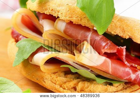 bread sandwich with slices of parma ham and arugula