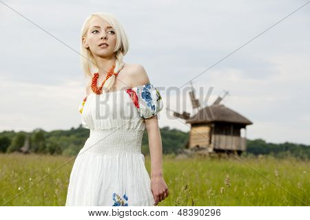 young rural woman standing at the green field