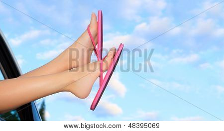 Female legs in pink sandals out from the car. Summer trip concept