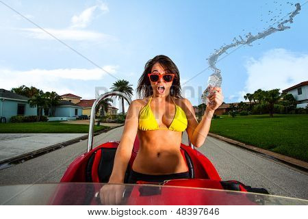 Young Brunette Woman Riding A Red Beach Car