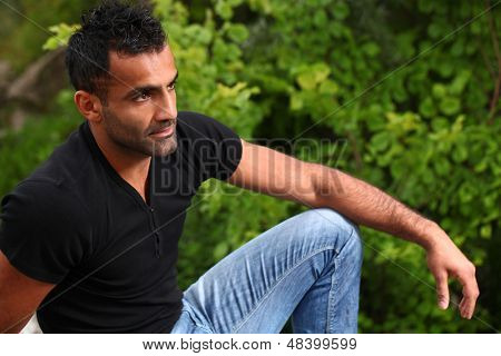 Portrait of a handsome man with fashionable haircut and beard who is sitting near the trees and looks afar