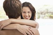 stock photo of eye-wink  - Smiling young woman winking while embracing man - JPG