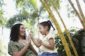 picture of patty-cake  - Happy girl and mother playing patty cake in park - JPG