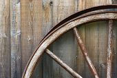stock photo of stagecoach  - Closeup view of wagon wheel and exterior wooden wall - JPG