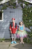 pic of pirate girl  - Full length portrait of a young boy in pirate costume and girl in fairy costume by shed - JPG