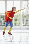 stock photo of extend  - Full length of a young boy in superhero costume with arm extended indoors - JPG
