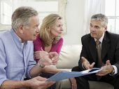 stock photo of revenue  - Mature couple sitting on sofa with financial advisor - JPG