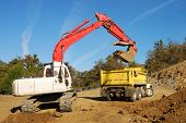 foto of track-hoe  - Large track hoe excavator filling a dump truck at a new commercial construction site - JPG