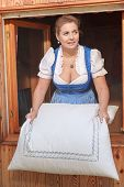 picture of milkmaid  - Young peasant woman in dirndl shakes the beds on the mountain - JPG