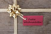 pic of weihnachten  - the german words Frohe Weihnachten which means merry christmas on a red label on a golden bow as background - JPG