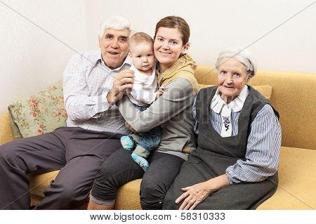Four generation family sitting on sofa