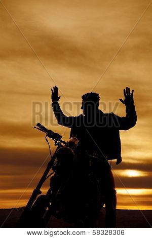 Silhouette Of A Man On A Motorcycle Hands Up