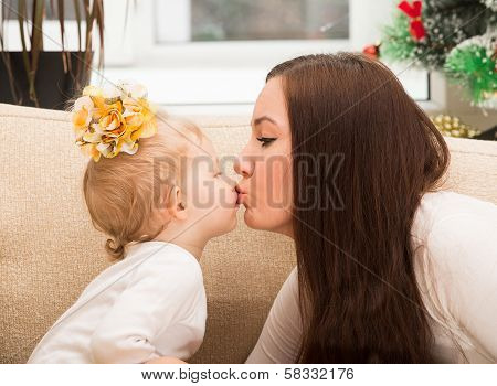 Happy Mom And Child Girl  Kissing At Home.
