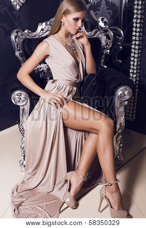 sexy blond in beige silk dress sitting on the black armchair