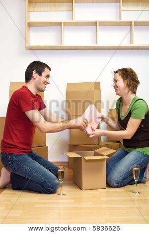 Feliz pareja desempaquetado y tostado en su nuevo hogar