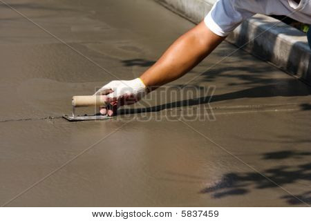 Construction Worker Laying Cement
