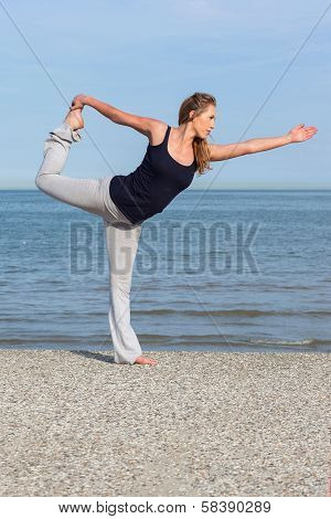 Beautiful Woman Doing Yoga At The Seaside