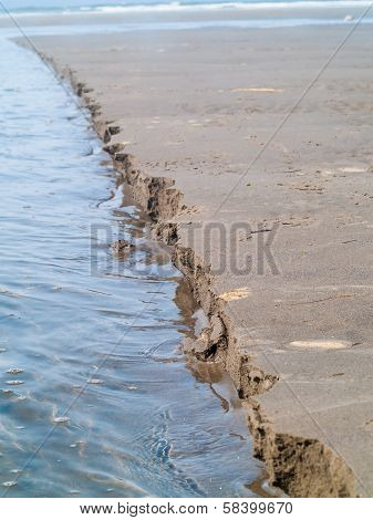 A Line Of Wet Sand Eroding At The Beach At The Water's Edge