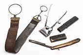 picture of trimmers  - Old and worn rusty razor razor case sharpening leather and a metal trimmer on a white background - JPG