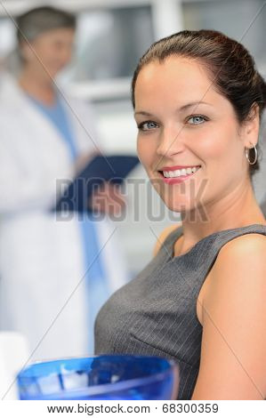 Elegant woman patient at dental surgery smiling dentist in background