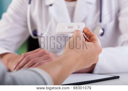 Female Hands With Positive Pregnancy Test At Doctor's Office