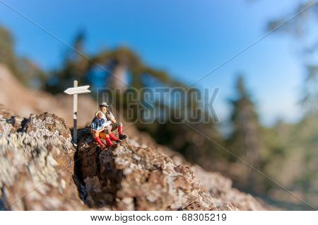 Two Hikers With Backpack Relaxing On Top Of A Mountain