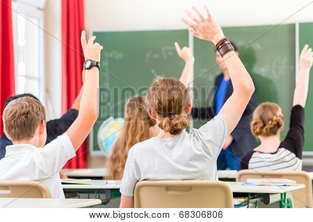 School class teacher giving lesson in front of a blackboard or board teaching students or pupils, they are raising their hands as they know all the answers