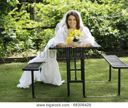 A beautiful young bride laying across a picnic table, the train of her gown drooping across a seat to the ground.