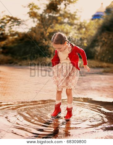 Kid Jumping Into A Puddle