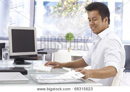 Young Asian businessman working in bright office, sitting at desk.