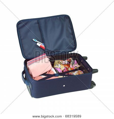 An opened suitcase packed with colorful cloth