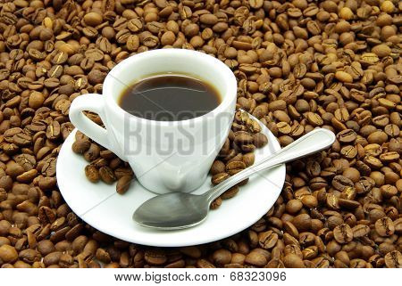 white cup with coffee costing on a coffee grain