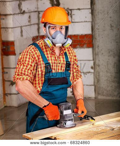 Man  in builder helmet with electric planer.