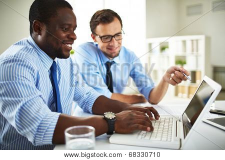 Image of two young businessmen using laptop at meeting