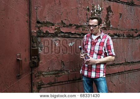 Young man drinks vodka outdoor