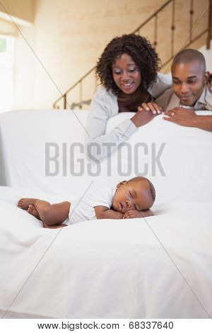 Baby boy sleeping peacefully on couch watched by parents at home in the living room