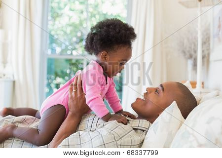 Happy father and baby girl lying on bed together at home in the bedroom