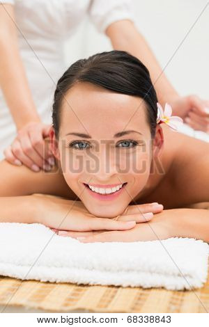 Peaceful brunette enjoying a herbal compress massage smiling at camera in the health spa