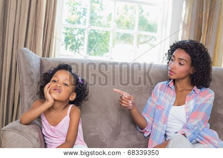 Pretty mother scolding her daughter on the couch at home in the living room