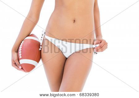 Fit girl in white bikini holding american football on white background