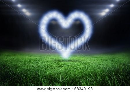 Cloud in shape of heart against football pitch with bright lights