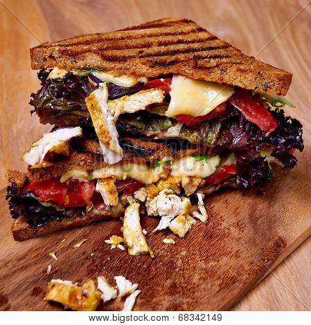 Chicken club sandwich on wooden board