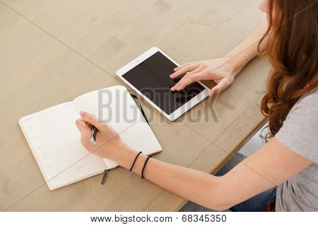 Home, study. Woman by the table with tablet