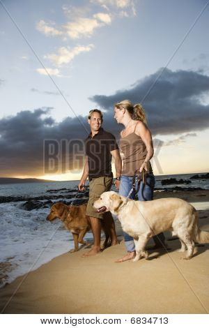 Couple Walking Dogs At The Beach