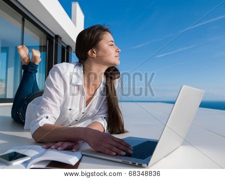 beautiful young woman relax and work on laptop computer  and read book at modern  home