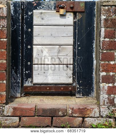 Small Locked Gate In A Brick Wall