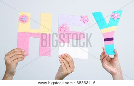 Hands holding up letters building word hey on grey background