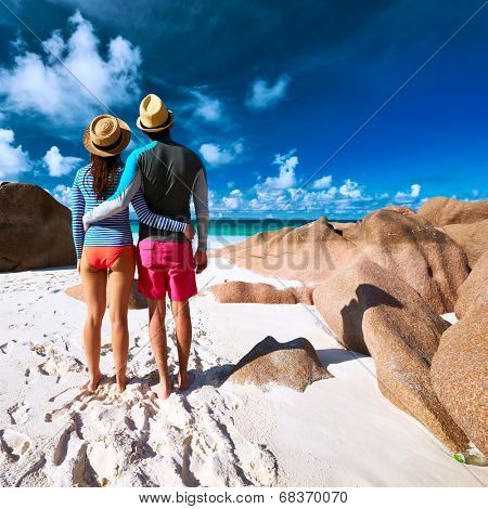 Couple on a tropical beach at Seychelles wearing rash guard
