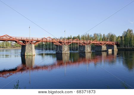 Red wooden bridge crosses a river in evening lit.
