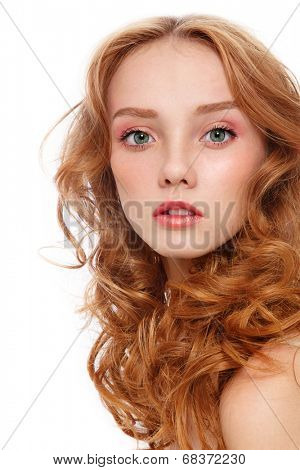 Young beautiful woman with long red curly hair and fresh make-up over white background